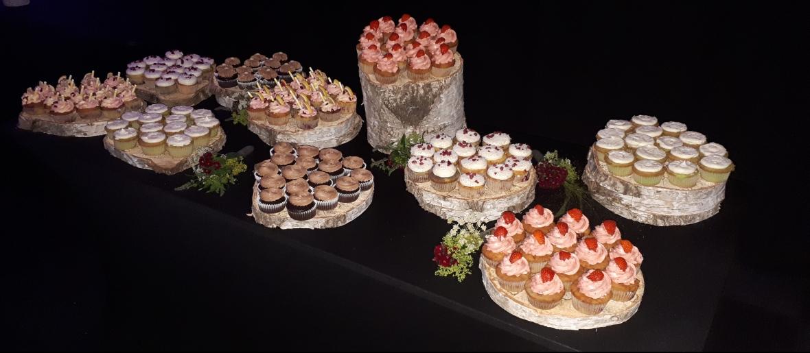 Aangeklede tafel met verschillende cupcakes.