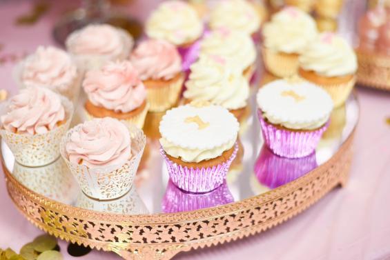De cupcakes van de 1e verjaardag in het thema wit, roze en goud.